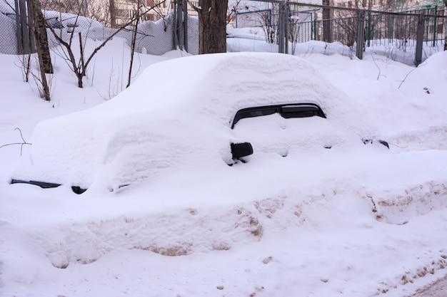 Samochód pokryty świeżym białym śniegiem, samochody pokryte śniegiem po śnieżycy