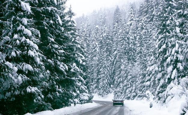 Samochód porusza się ostrożnie po górskiej drodze pokrytej śniegiem