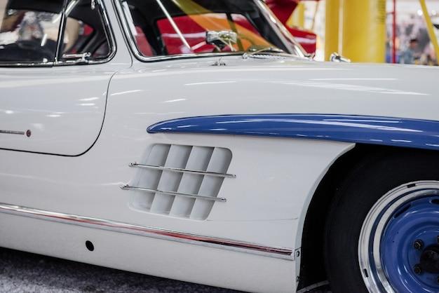 Samochód retro pomalowany na biało i niebiesko stoi na wystawie w pomieszczeniu indoor