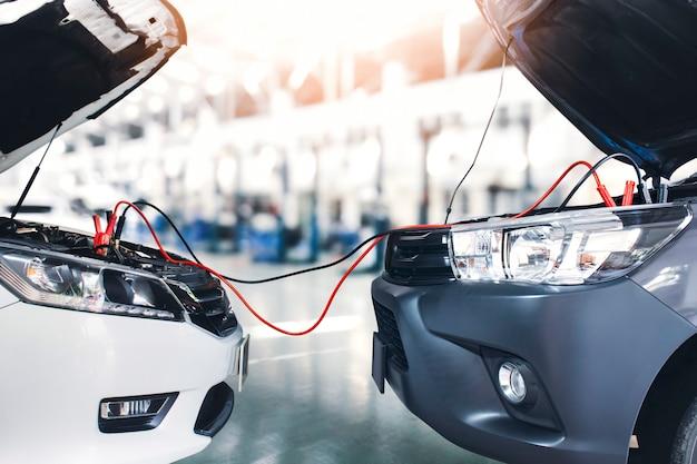 Samochód sedan zworka kable akumulatora do pickupa w warsztacie naprawczym