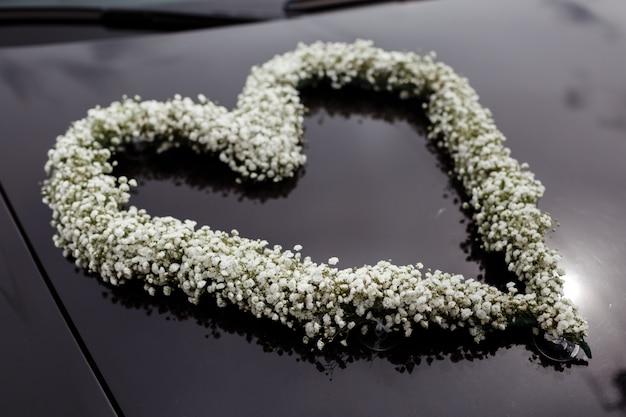 Samochód ślubny ozdobiony sercem białych kwiatów