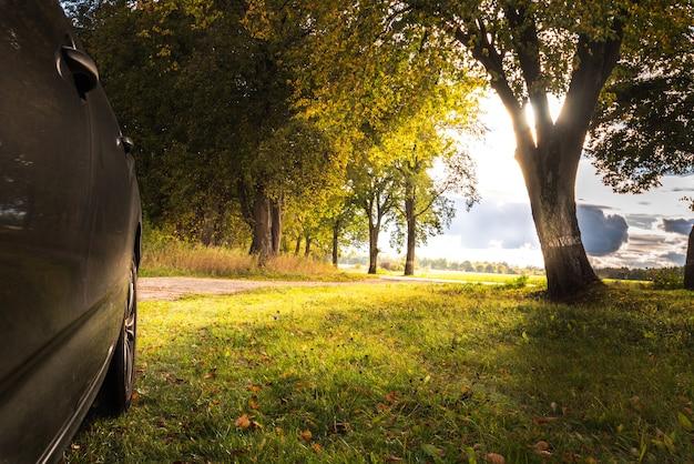 Samochód stoi na poboczu drogi w słoneczny dzień na wsi