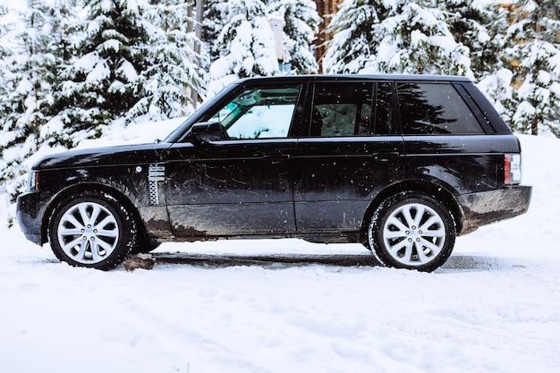 Samochód suv w zaśnieżonej przestrzeni kopii lasu