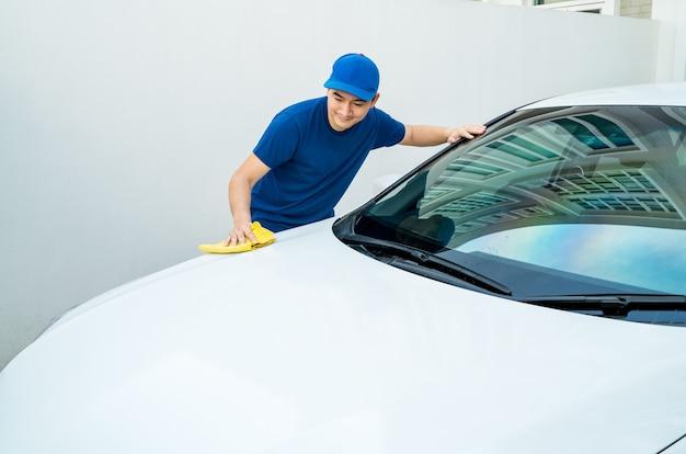 Samochód szczegółowo, człowiek w niebieskim mundurze oczyścić biały samochód