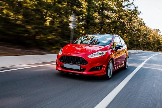 Samochód testowy czerwony sedan jazdy na autostradzie.