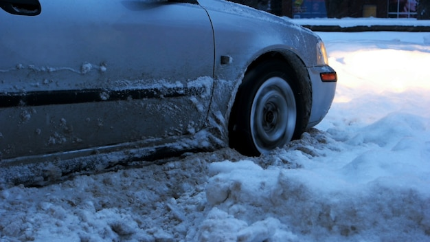 Samochód utknął na śniegu. zamknij się z koła samochodu zatrzymane w dryf śniegu. nieoczyszczone ulice z zaspą śnieżną po silnej śnieżycy.