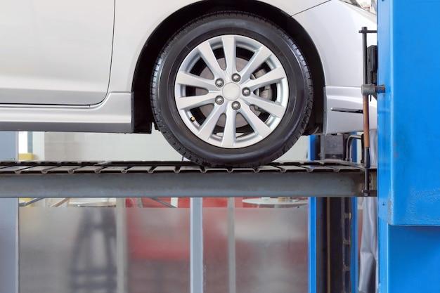 Samochód w garażu serwisowym z mechanicznymi narzędziami do naprawy samochodu, mechanik samochodowy pracujący w centrum serwisowym samochodu