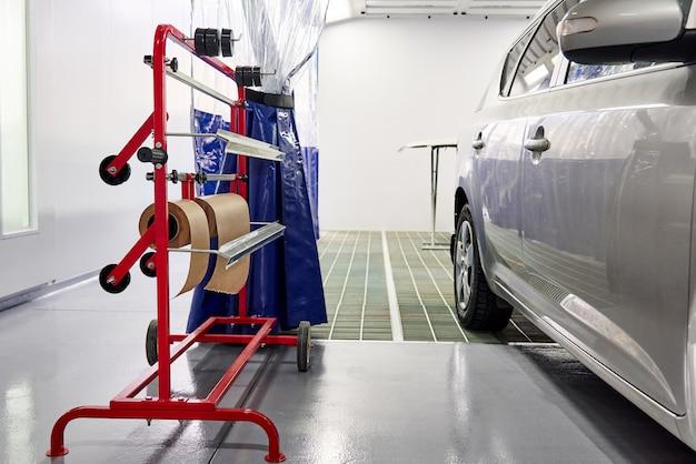 Samochód w kabinie lakierniczej w warsztacie samochodowym, gotowy do pomalowania