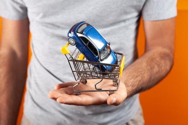 Samochód w koszu w rękach mężczyzny na pomarańczowym tle