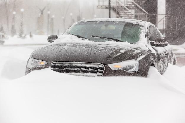 Samochód w mieście utknął w śniegu i jest zaśnieżony