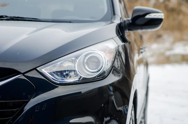 Samochód w przyrodzie. reflektor czarnego samochodu