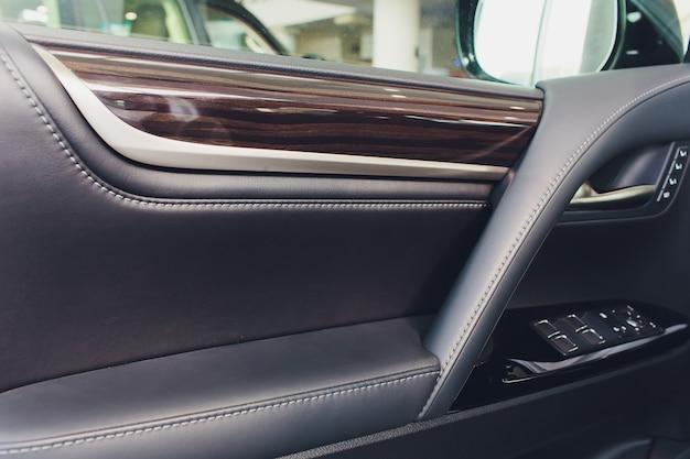 Samochód w środku. wnętrze prestiżowego nowoczesnego samochodu. klimatyzacja, wysokiej jakości głośniki, pamięć siedzenia, lusterko boczne dźwigni drzwi. biały kokpit z drewnianą metalową dekoracją, niebieskie światło otoczenia.