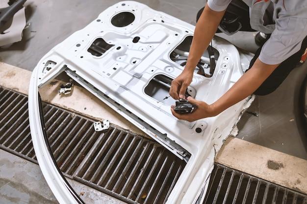 Samochód w warsztacie samochodowym mechanik naprawiający lakierowanie drzwi i karoserii samochodu z miękkim ogniskiem i nad światłem w miękkim ogniskowaniu i nad światłem w tle