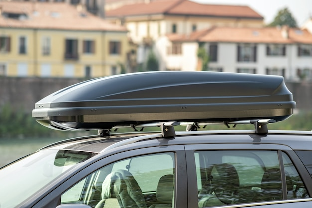 Samochód z bagażnikiem dachowym zaparkowany na ulicy na parkingu.