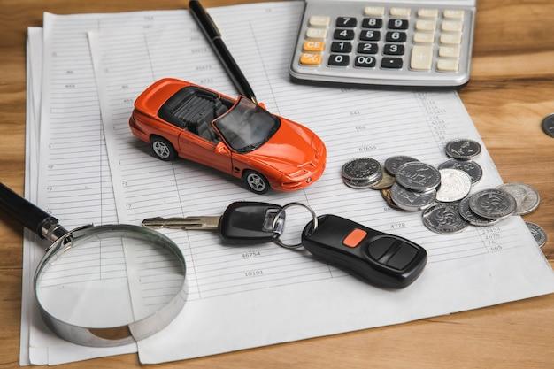 Samochód z kluczem i monetami na dokumencie