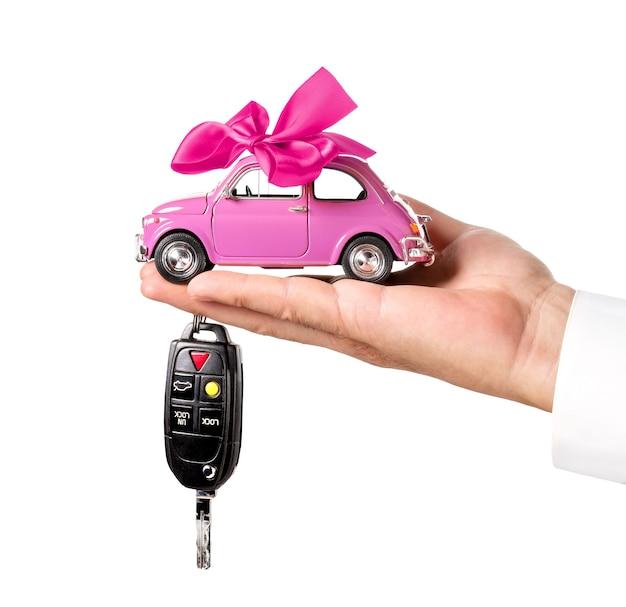 Samochód z łukiem i kluczem na ręce dealera na białym tle. koncepcja zakupu samochodu