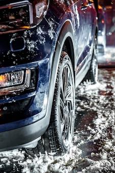 Samochód z oponami zimowymi na stojaku, czas zimowy, śnieg i lód.