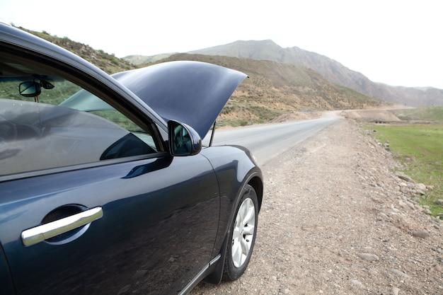 Samochód z otwartą maską na poboczu drogi w ciągu dnia