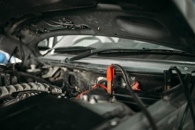 Samochód z otwartą maską, przewód do ładowania akumulatora