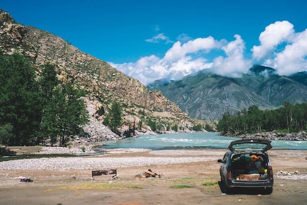 Samochód z otwartym dużym bagażnikiem w pobliżu górskiej rzeki z turkusową wodą.