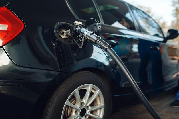 Samochód z pistoletem w zbiorniku zbliżenie, tankowanie na stacji benzynowej, uzupełnianie paliwa, nikt. serwis tankowania benzyny, benzyny lub oleju napędowego, tankowanie ropy naftowej