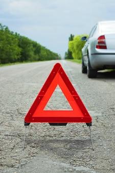 Samochód z problemami i czerwony trójkąt ostrzegający innych użytkowników drogi