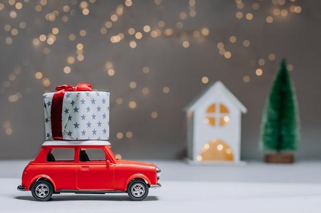 Samochód zabiera do domu duży prezent na dachu. na tle drzewa i świateł. koncepcja na temat nowego roku i bożego narodzenia.