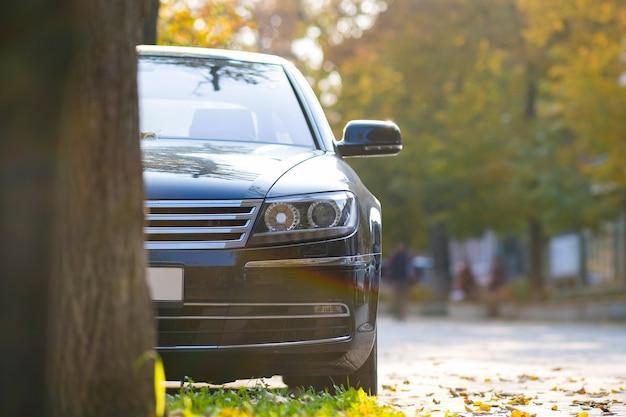 Samochód zaparkowany na stronie ulicy miasta w jesienny dzień z niewyraźne ludzi chodzących w strefie dla pieszych.
