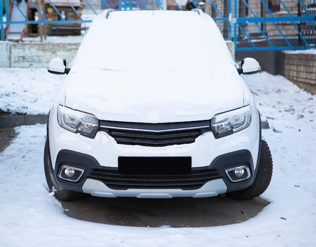 Samochód zaparkowany na ulicy pokryty jest świeżym, białym śniegiem