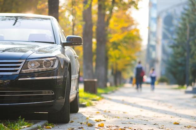 Samochód zaparkowany po stronie ulicy miasta w jasny jesienny dzień z zamazanymi ludźmi spacerującymi w strefie dla pieszych