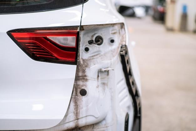 Samochód zderzył się z tyłu nadwozia z bliska, nowoczesny biały samochód typu suv został uszkodzony z tyłu i naprawiany w garażu.
