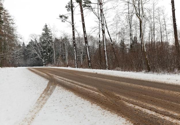 Samochodem droga asfaltowa, na której topniał śnieg. na śniegu widoczne ślady kół auta. na poboczu drogi rośnie las.