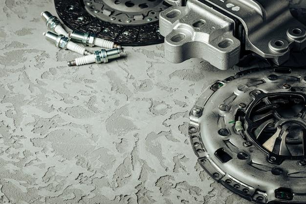 Samochodowe części na popielatym textured betonowym tle