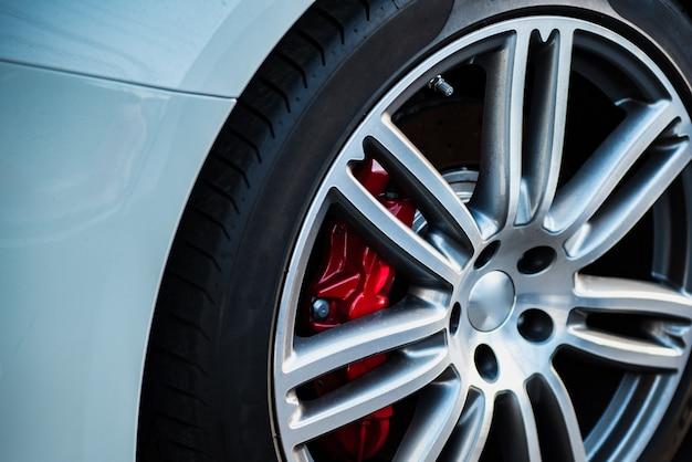 Samochodowe felgi aluminiowe z oponą i klockami hamulcowymi.