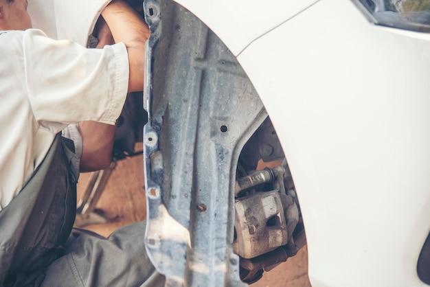 Samochodowe mechaniczne z bliska ręce ustalające naprawy samochodów. warsztat mechanika