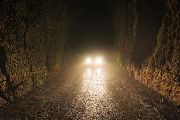 Samochodowi reflektory przy nocą w mgłowej drodze