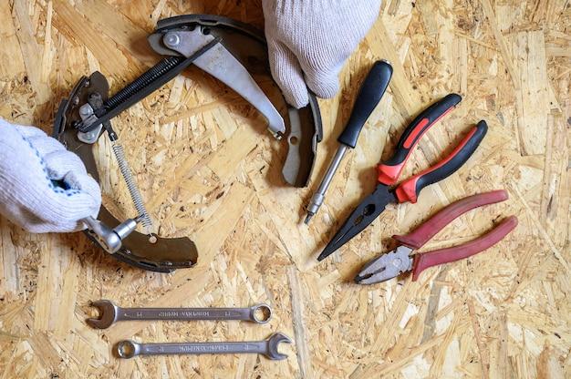 Samochodowy hamulec bębnowy zdemontowany w męskich rękawiczkach i zestaw różnych ręcznych narzędzi naprawczych