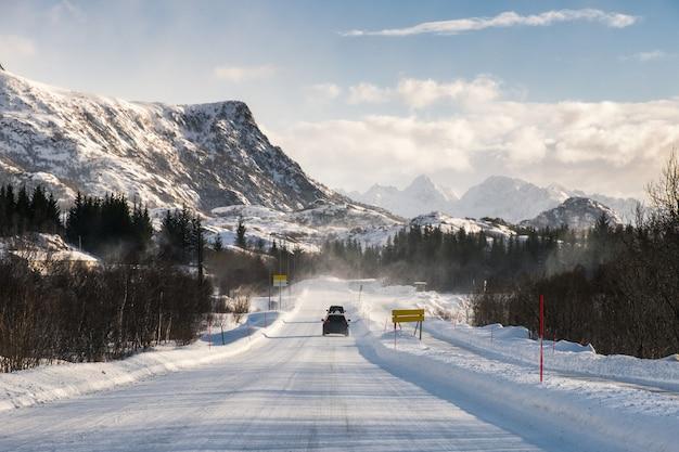 Samochodowy jeżdżenie na śnieżnej drodze z pasmem górskim