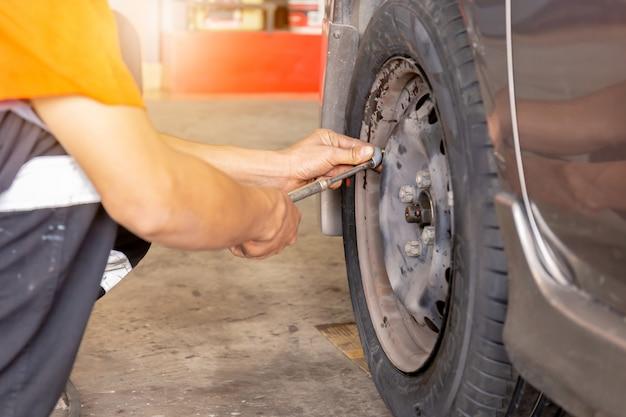Samochodowy mechanik sprawdza ciśnienie naciska pracę przy remontowym stacją obsługi