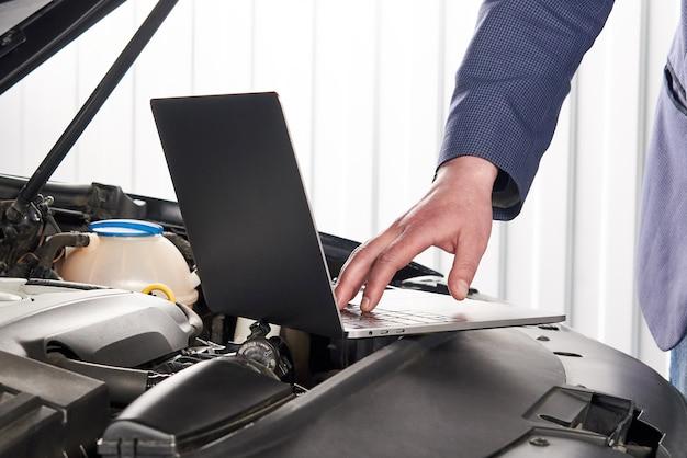 Samochodowy mechanik używa komputer w auto remontowym sklepie