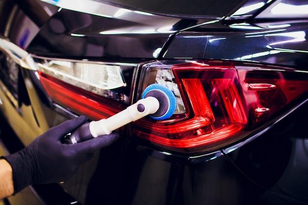 Samochodowy połysku wosku pracownik wręcza mienie polerowaczu i połysku samochodu wyszczególnia lub waliduje pojęcie taillight czerwieni samochód