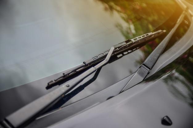 Samochodowy wiper samochód parkujący na ulicznym światła słonecznego tle