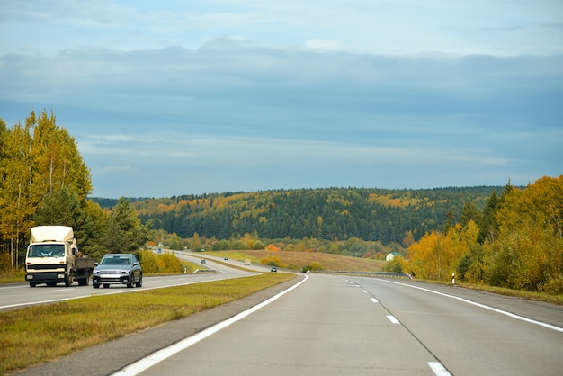 Samochody jeżdżą na górskiej autostradzie jesienią