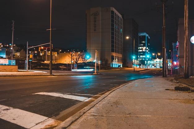Samochody na drodze w pobliżu budynków w nocy