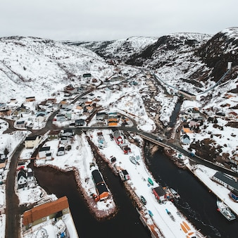 Samochody na drodze w pobliżu góry pokryte śniegiem w ciągu dnia