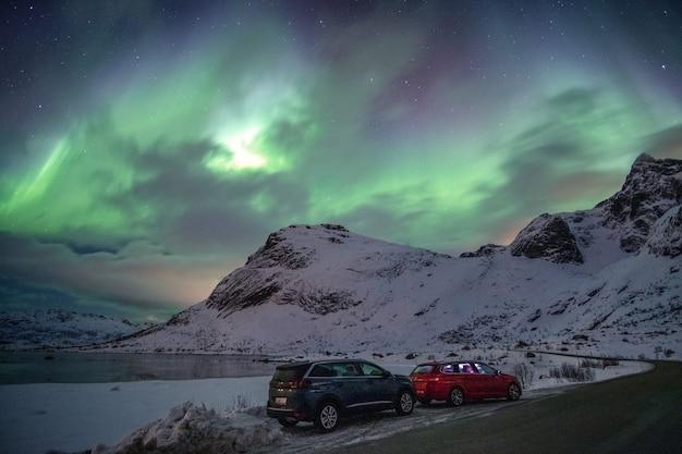 Samochody parkujące na wiejskiej drodze z zorzą polarną na niebie na lofotach, wyspy