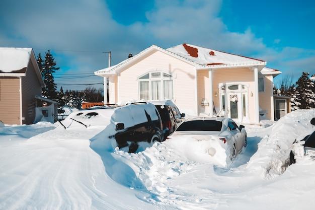 Samochody pokryte śniegiem przed domem