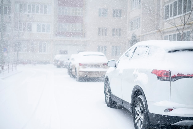 Samochody pokryte śniegiem zimą, na zewnątrz burzowa pogoda