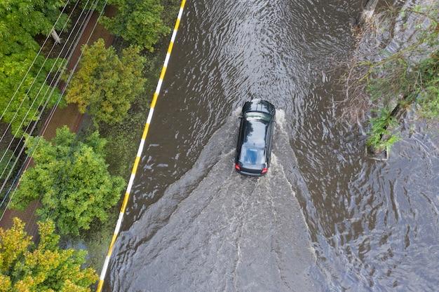 Samochody poruszają się po mocno zalanej ulicy po nienormalnej ulewie.
