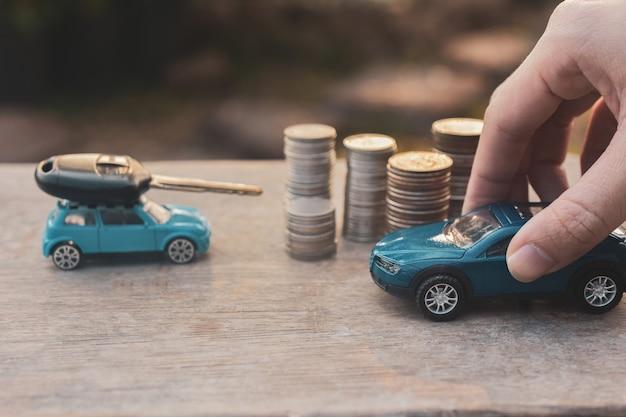 Samochody zabawkowe, stosy monet i kluczyk
